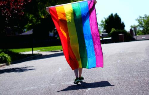 person-walking-while-holding-rainbow-colored-flag-2433122-scaled